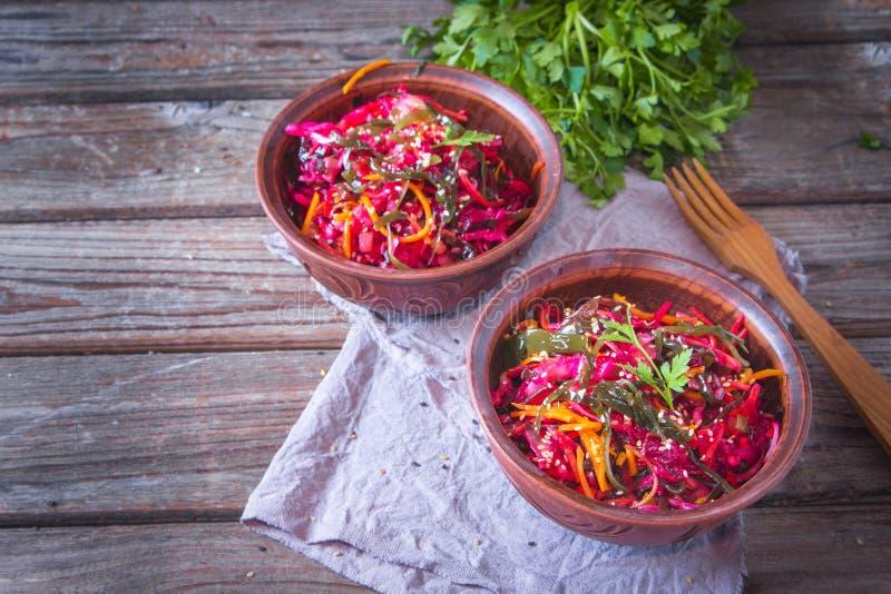 Διαιτητική σαλάτα με το κατσαρό λάχανο θάλασσας, τα καρότα, τα τεύτλα και το σουσάμι, που ψεκάζονται με το ελαιόλαδο στο αγροτικό στοκ φωτογραφίες