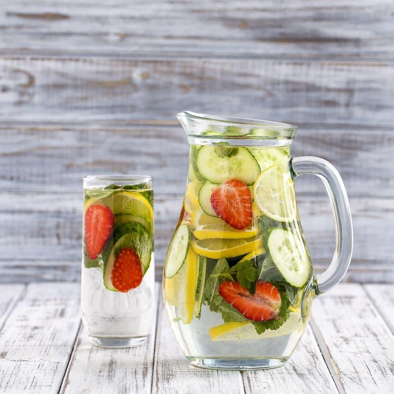 Διαιτητικό ποτό detox με το χυμό λεμονιών, κόκκινα φύλλα φραουλών, αγγουριών και μεντών στο σαφές νερό με τον πάγο στοκ φωτογραφίες με δικαίωμα ελεύθερης χρήσης