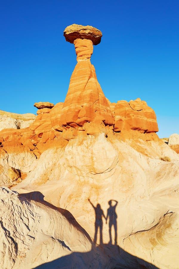Διακινούμενο ζεύγος που κάνει την αστεία εικόνα κάτω από το σχηματισμό βράχου hoodoo στην Αριζόνα, ΗΠΑ στοκ εικόνα