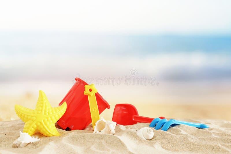 Διακοπές εικόνα διακοπών και καλοκαιριού με τα ζωηρόχρωμα παιχνίδια παραλιών για το παιδί πέρα από την άμμο στοκ φωτογραφία με δικαίωμα ελεύθερης χρήσης