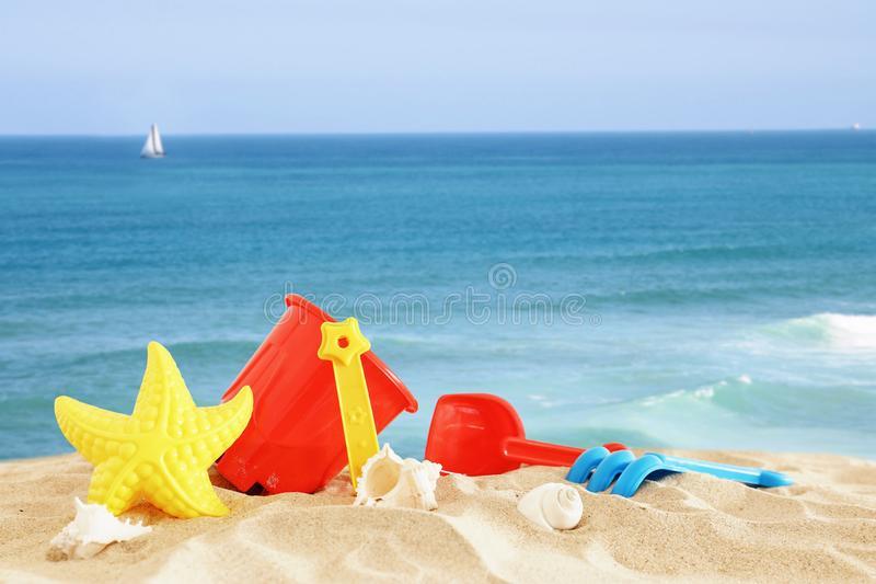 Διακοπές εικόνα διακοπών και καλοκαιριού με τα ζωηρόχρωμα παιχνίδια παραλιών για το παιδί πέρα από την άμμο στοκ εικόνες