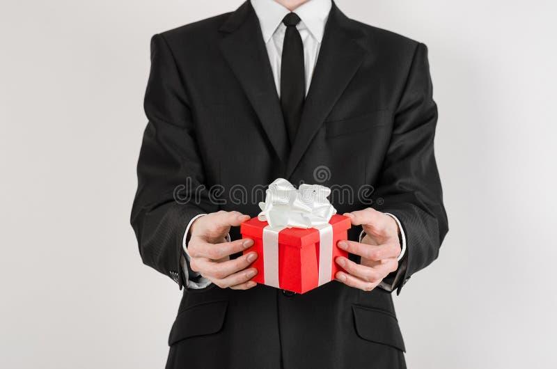 Διακοπές και δώρα θέματος: ένα άτομο σε ένα μαύρο κοστούμι κρατά το αποκλειστικό δώρο τυλιγμένο στο κόκκινο κιβώτιο με την άσπρη  στοκ εικόνα