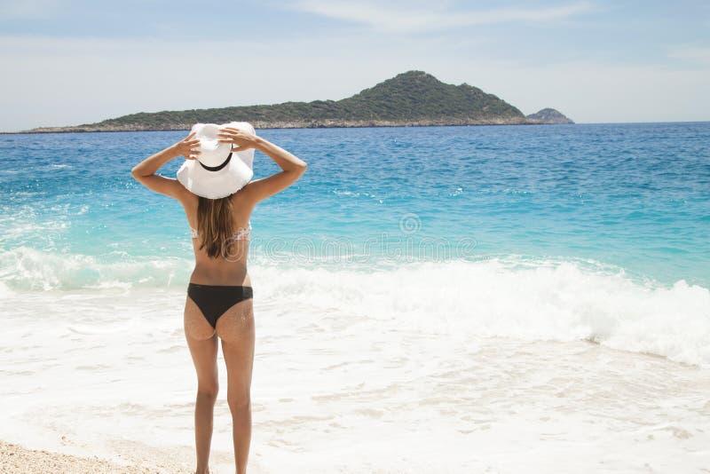 Διακοπές παραλιών Καυτή όμορφη γυναίκα στο καπέλο ήλιων και μπικίνι που στέκεται με τα όπλα της που αυξάνονται στην επικεφαλής απ στοκ εικόνα