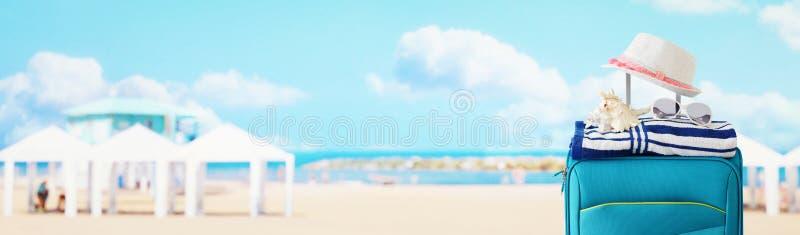 Διακοπές r μπλε βαλίτσα με το θηλυκό καπέλο, το κοχύλι θάλασσας, τα γυαλιά ηλίου και την πετσέτα παραλιών μπροστά από το τροπικό  στοκ φωτογραφίες