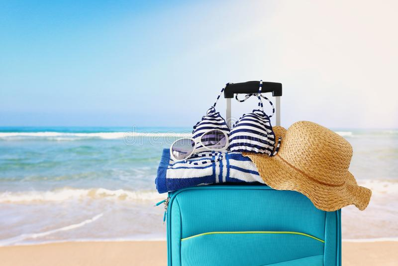 Διακοπές r μπλε βαλίτσα με το θηλυκό καπέλο, το μπικίνι γυαλιών ηλίου και την πετσέτα παραλιών μπροστά από το τροπικό υπόβαθρο στοκ φωτογραφίες