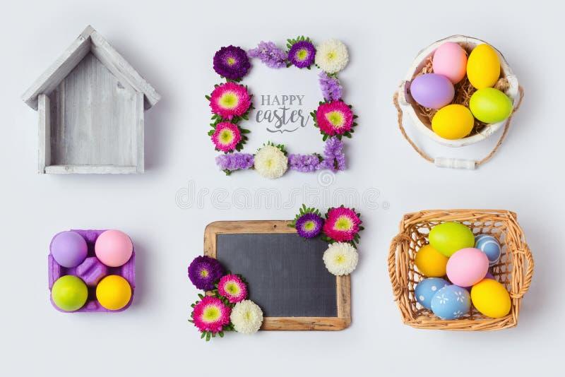 Διακοσμήσεις αυγών διακοπών Πάσχας, πλαίσια λουλουδιών και καλάθι για τη χλεύη επάνω στο σχέδιο προτύπων επάνω από την όψη στοκ φωτογραφία