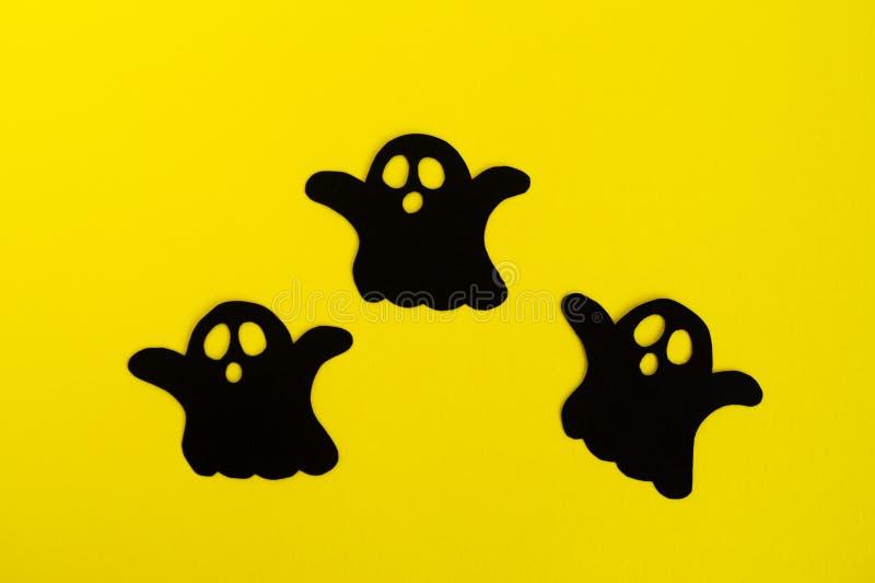Διακοσμήσεις διακοπών για αποκριές Τρία μαύρα φαντάσματα εγγράφου σε ένα κίτρινο υπόβαθρο, τοπ άποψη στοκ εικόνες