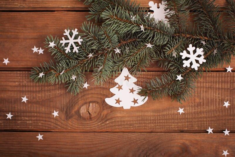 Διακοσμήσεις καρτών Χαρούμενα Χριστούγεννας στην κοπή εγγράφου με το έλατο στοκ εικόνες