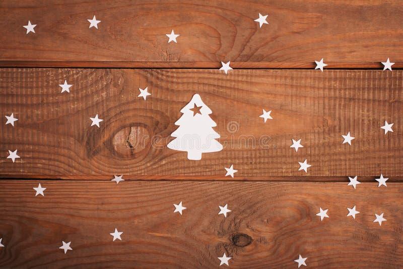 Διακοσμήσεις καρτών Χαρούμενα Χριστούγεννας στην κοπή εγγράφου πέρα από το woodeno στοκ φωτογραφία με δικαίωμα ελεύθερης χρήσης