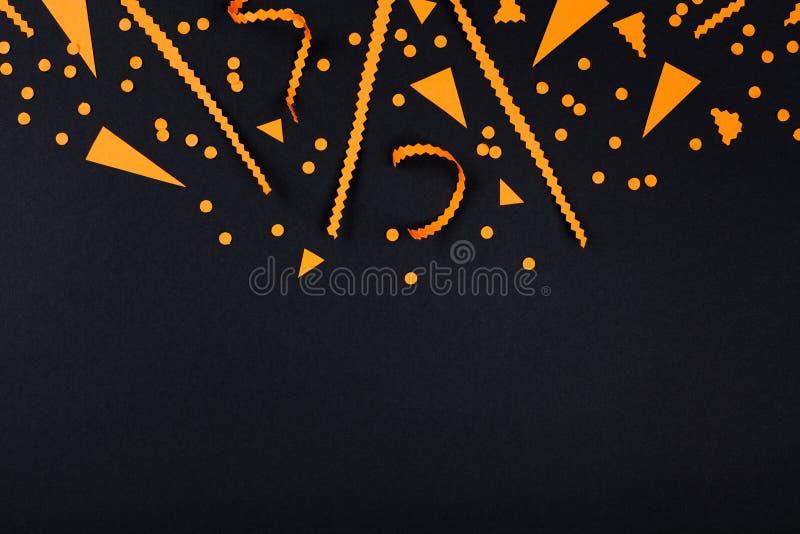 Διακοσμήσεις κομμάτων αποκριών από το κομφετί στη μαύρη τοπ άποψη υποβάθρου επίπεδος βάλτε το ύφος στοκ εικόνες