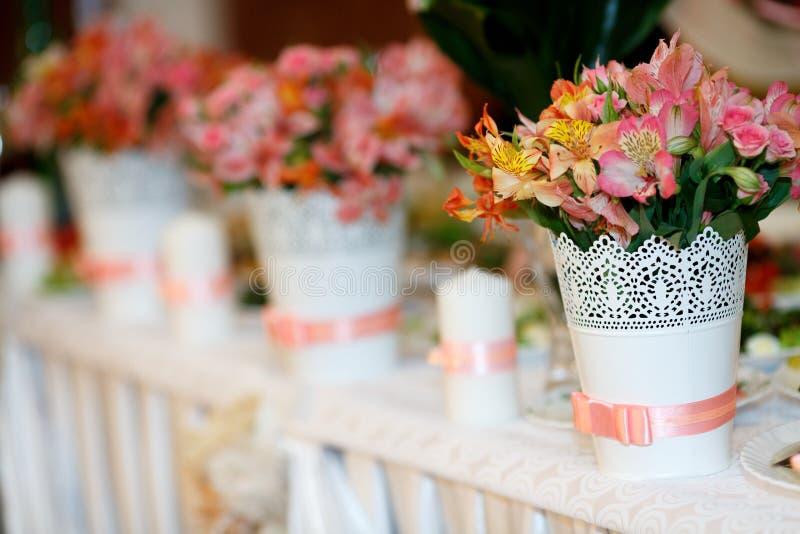 Διακοσμήσεις λουλουδιών με τη ρόδινη στάση κορδελλών στο γαμήλιο πίνακα στοκ εικόνες με δικαίωμα ελεύθερης χρήσης