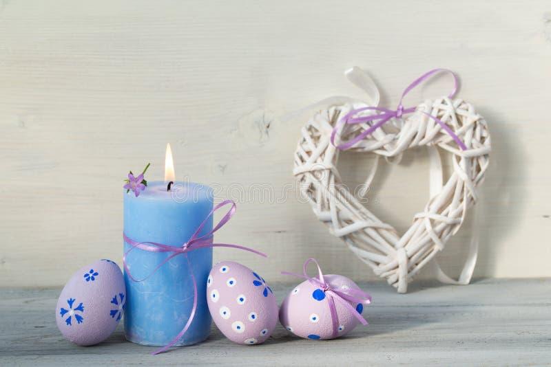 Διακοσμήσεις Πάσχας με τα αυγά Πάσχας, το καίγοντας κερί και την καρδιά σε ένα ξύλινο υπόβαθρο στοκ εικόνες