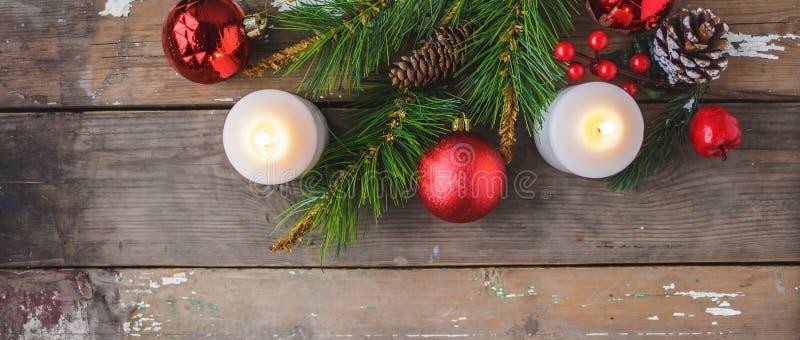 Διακοσμήσεις Χριστουγέννων, καίγοντας κεριά, ερυθρελάτες σε ένα ξύλινο υπόβαθρο Νέα έννοια έτους `s κάρτα στοκ φωτογραφία