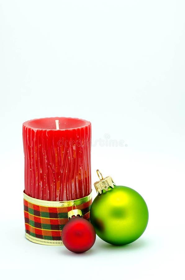Διακοσμήσεις Χριστουγέννων - κόκκινο κερί και κόκκινες και χρυσές διακοσμήσεις στοκ φωτογραφία