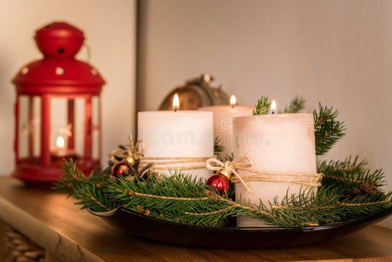 Διακοσμήσεις Χριστουγέννων με τα αναμμένα κεριά σε ένα τραπεζάκι σαλονιού στοκ εικόνα με δικαίωμα ελεύθερης χρήσης