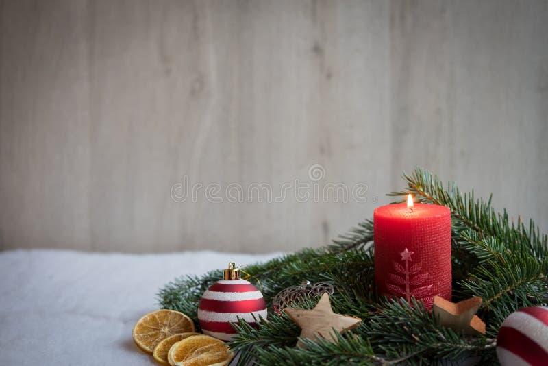Διακοσμήσεις Χριστουγέννων με το χιόνι, το δέντρο πεύκων και το κόκκινο κερί στοκ εικόνες