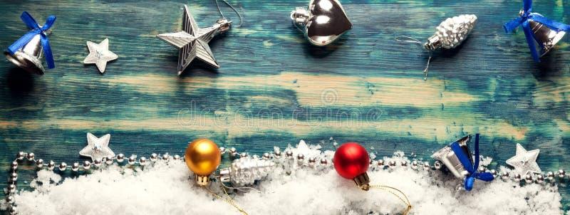 Διακοσμήσεις Χριστουγέννων σε έναν πίνακα στο χιόνι με τους συμπαθητικούς εορταστικούς φωτισμούς Χριστουγέννων υποβάθρου στοκ φωτογραφίες με δικαίωμα ελεύθερης χρήσης