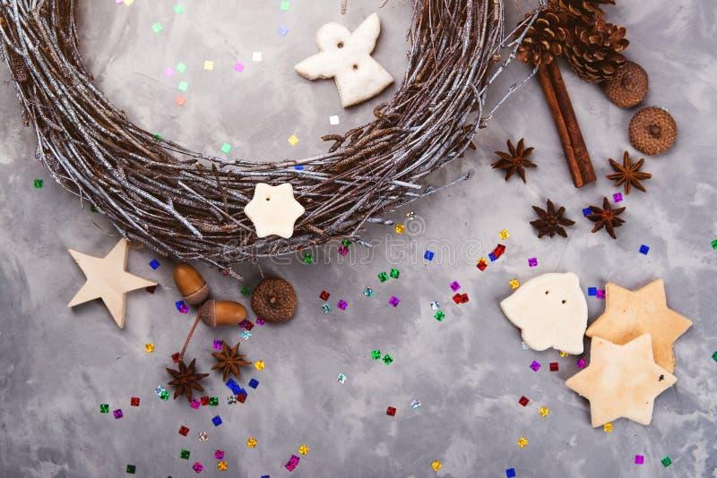 Διακοσμήσεις Χριστουγέννων στο συγκεκριμένο υπόβαθρο Ξύλινες στεφάνι, μελόψωμο, βελανίδια, πεύκο και κανέλα διάστημα αντιγράφων Π στοκ εικόνες