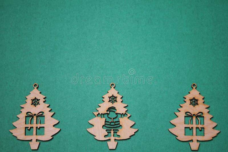 Διακοσμήσεις Χριστουγέννων υπό μορφή ξύλινων χριστουγεννιάτικων δέντρων σε ένα πράσινο υπόβαθρο στοκ φωτογραφίες με δικαίωμα ελεύθερης χρήσης
