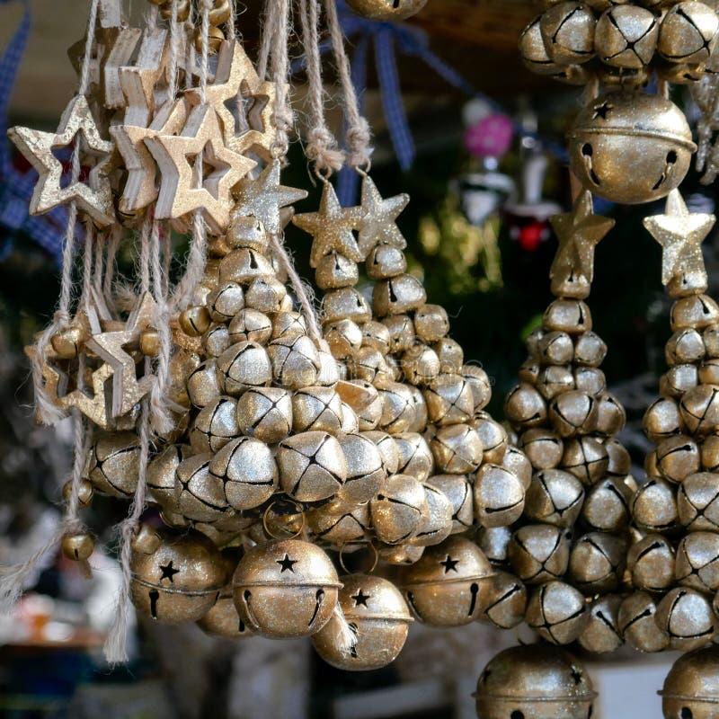 Διακοσμήσεις Χριστουγέννων φιαγμένες από χρυσά στρογγυλά κουδούνια και χρυσά ξύλινα αστέρια που κρεμούν στην αγορά για την πώληση στοκ φωτογραφίες