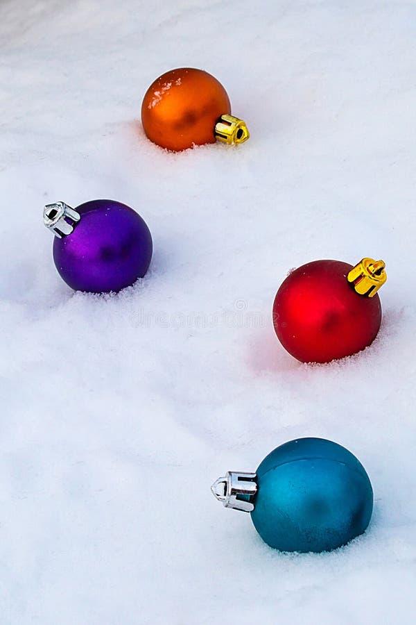 Διακοσμήσεις χριστουγεννιάτικων δέντρων στο άσπρο χιόνι οι σφαίρες χρωμάτισαν πο&lambd στοκ εικόνες με δικαίωμα ελεύθερης χρήσης