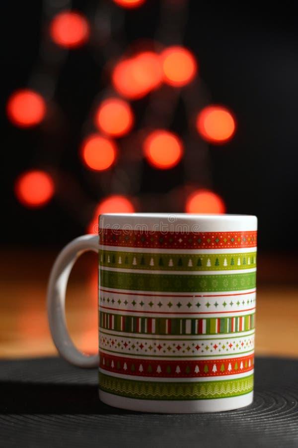 Διακοσμημένη Χριστούγεννα κούπα με τα κόκκινα φώτα στο υπόβαθρο στοκ εικόνες με δικαίωμα ελεύθερης χρήσης