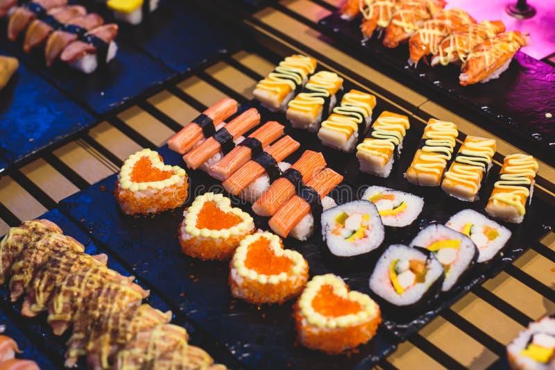 Διακοσμημένο να εξυπηρετήσει τον πίνακα συμποσίου με τα διαφορετικά ασιατικά σούσια κυλά και την κατάταξη πιάτων σουσιών nigiri σ στοκ εικόνες