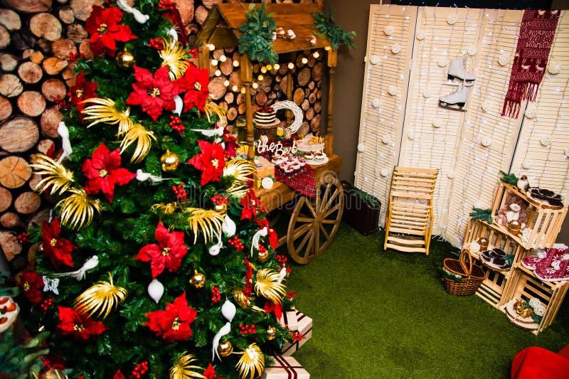 Διακοσμημένο χριστουγεννιάτικο δέντρο και ένας πίνακας με τα γλυκά στοκ εικόνες