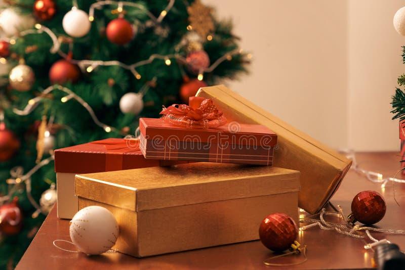 Διακοσμημένο χριστουγεννιάτικο δέντρο με τις ζωηρόχρωμα σφαίρες και τα κιβώτια δώρων στο σπίτι στοκ φωτογραφία