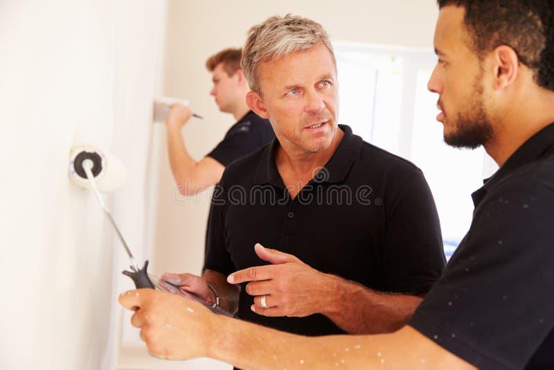 Διακοσμητής που καθοδηγεί το συνάδελφο που χρωματίζει ένα δωμάτιο στοκ φωτογραφίες