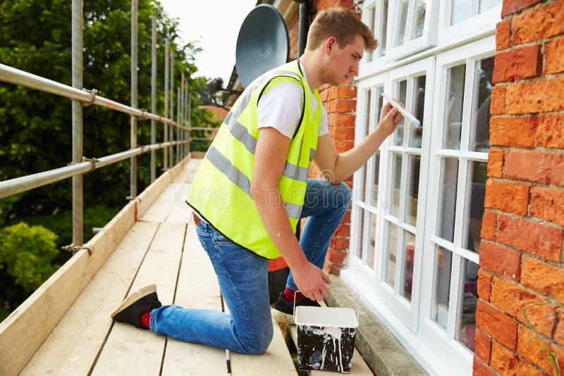 Διακοσμητής στα υλικά σκαλωσιάς που χρωματίζει τα εξωτερικά παράθυρα σπιτιών στοκ φωτογραφίες