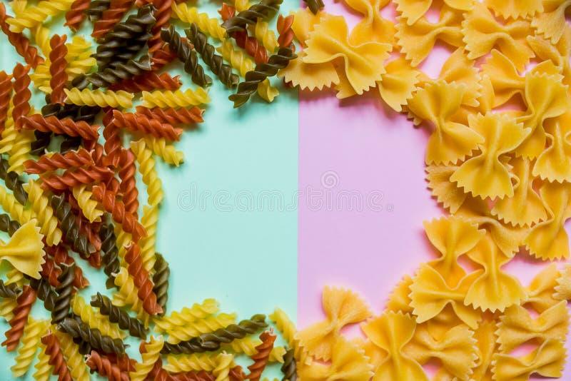 Διακοσμητικά σύνορα φιαγμένα από διάφορα ακατέργαστα ζυμαρικά Εύγευστο ιταλικό υπόβαθρο τροφίμων Επίπεδος βάλτε των άψητων coolor στοκ φωτογραφία με δικαίωμα ελεύθερης χρήσης