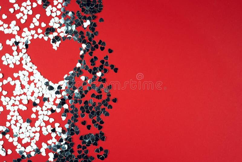 Διακοσμητικές ασημένιες καρδιές σε ένα κόκκινο υπόβαθρο στοκ φωτογραφίες