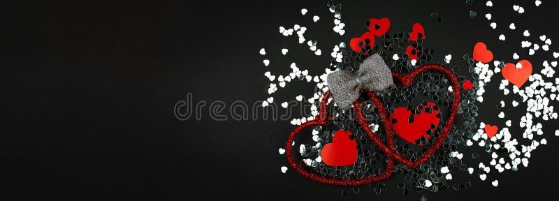 Διακοσμητικές κόκκινες καρδιές και ασημένιο κομφετί σε ένα μαύρο υπόβαθρο στοκ φωτογραφία με δικαίωμα ελεύθερης χρήσης