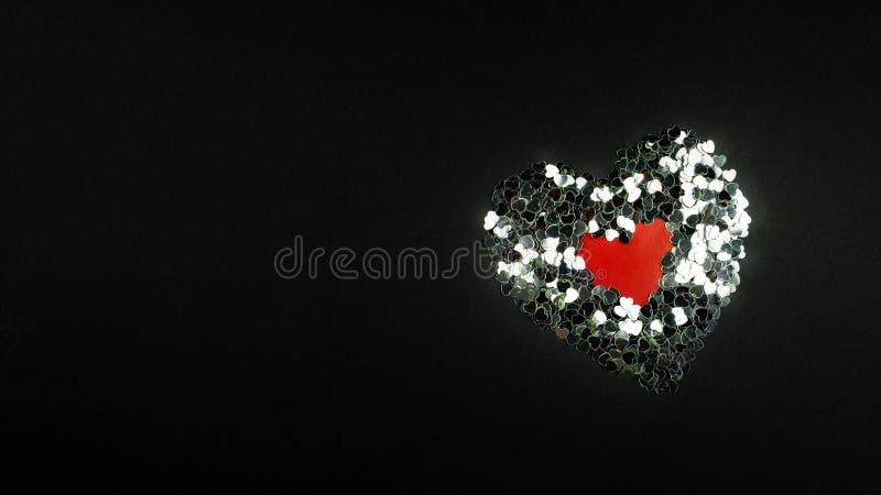 Διακοσμητικές κόκκινες καρδιές και ασημένιο κομφετί σε ένα μαύρο υπόβαθρο στοκ εικόνα με δικαίωμα ελεύθερης χρήσης