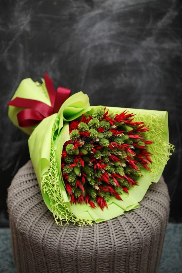 Διακοσμητική ανθοδέσμη των κόκκινων και πράσινων ξηρών λουλουδιών r στοκ φωτογραφίες