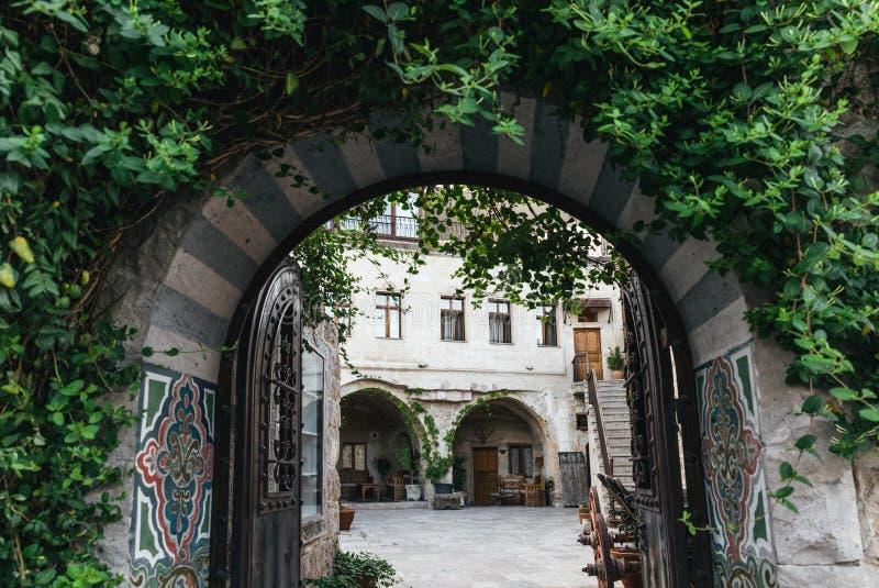 διακοσμητική αψίδα με τις ανοικτές πύλες και τα πράσινα φύλλα σε ιστορικό στοκ εικόνες