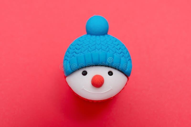 Διακοσμητική κούκλα Χριστουγέννων του χιονανθρώπου στο κόκκινο στοκ φωτογραφίες