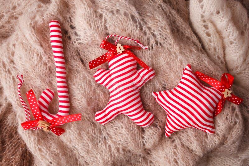 Διακοσμητικοί κάλαμος καραμελών Χριστουγέννων handcraft, αστέρι και άτομο μελοψωμάτων στο μάλλινο υπόβαθρο, αγροτικό υπόβαθρο Χαρ στοκ εικόνες
