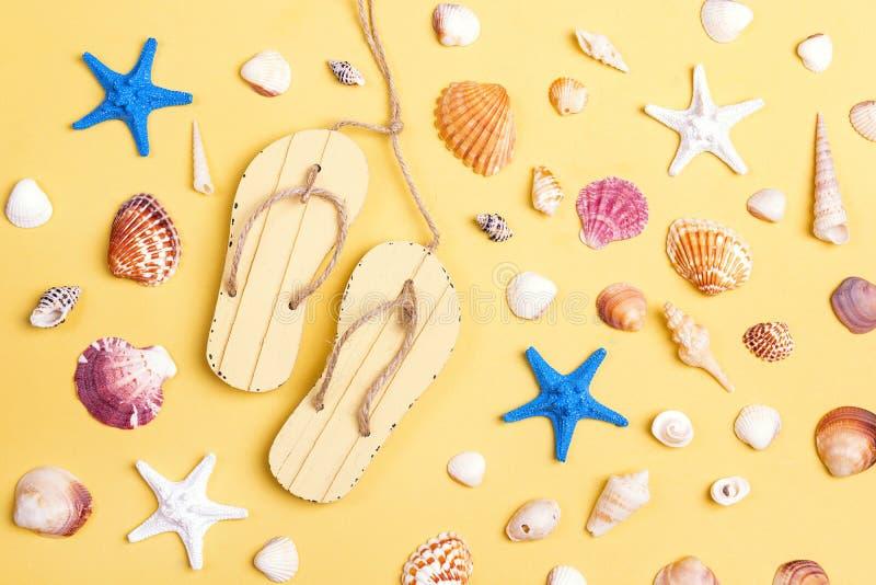 Διακοσμητικοί sandshoes, θαλασσινά κοχύλια και αστερίας στο κίτρινο backgrou στοκ φωτογραφίες με δικαίωμα ελεύθερης χρήσης