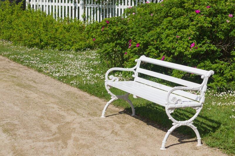 Διακοσμητικός άσπρος πάγκος στον κήπο στοκ φωτογραφία με δικαίωμα ελεύθερης χρήσης