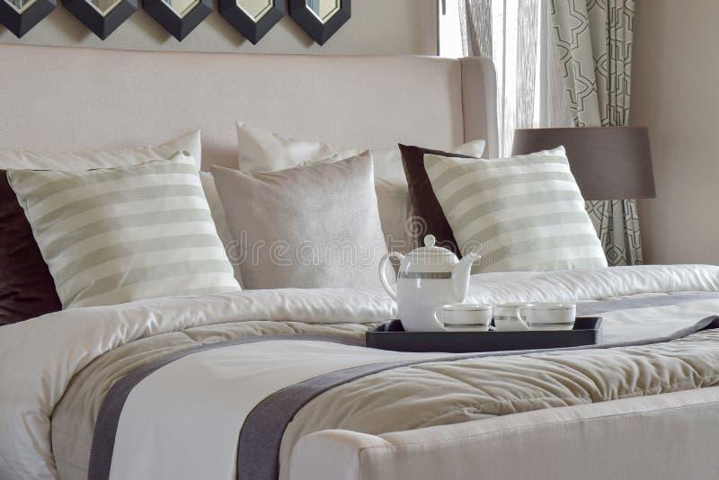 Διακοσμητικός δίσκος του συνόλου τσαγιού στο κρεβάτι στη σύγχρονη κρεβατοκάμαρα στοκ εικόνα με δικαίωμα ελεύθερης χρήσης