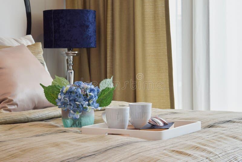 Διακοσμητικός δίσκος του φλυτζανιού και του βιβλίου τσαγιού στη μοντέρνη κρεβατοκάμαρα στοκ φωτογραφία με δικαίωμα ελεύθερης χρήσης