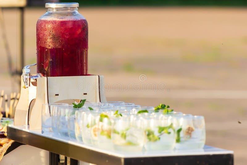 Διακοσμητικός υπαίθριος σταθμός ποτών κομμάτων με τα μικρά μπουκάλια και τη σπιτική λεμονάδα ροδάκινων στοκ φωτογραφία με δικαίωμα ελεύθερης χρήσης