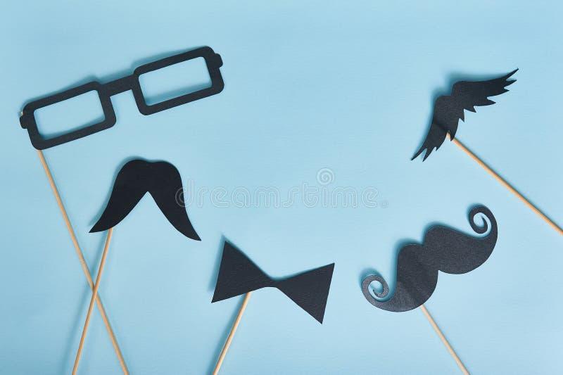 Διακοσμητικό άτομο mustache και μαύρα γυαλιά σε ένα ανοικτό μπλε υπόβαθρο εγγράφου τοπ άποψη για τη ευχετήρια κάρτα με τη θέση γι στοκ φωτογραφία με δικαίωμα ελεύθερης χρήσης