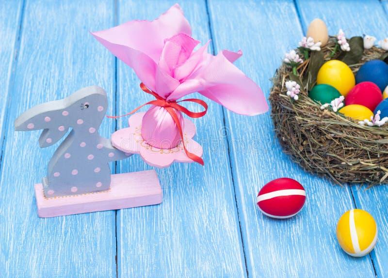 Διακοσμητικό λαγουδάκι Πάσχας με ένα εορταστικό αυγό στο υπόβαθρο μιας φωλιάς με τα πολύχρωμα αυγά κοτόπουλου σε ένα ξύλινο υπόβα στοκ εικόνες