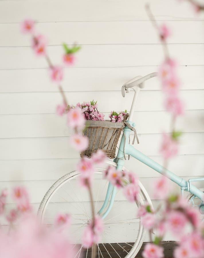 Διακοσμητικό ποδήλατο με ένα καλάθι των λουλουδιών στοκ εικόνα