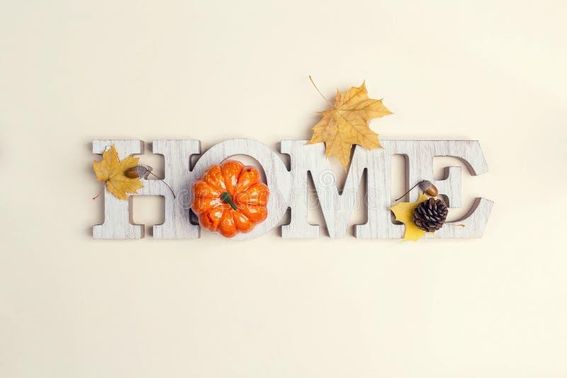 Διακοσμητικό σπίτι λέξης με την κολοκύθα και πεσμένα φύλλα επάνω στο μπεζ στοκ φωτογραφίες με δικαίωμα ελεύθερης χρήσης