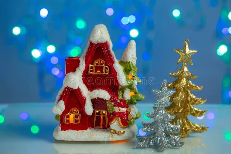 Διακοσμητικό χαριτωμένο κόκκινο σπίτι με το χριστουγεννιάτικο δέντρο στο μπλε λαμπιρίζοντας υπόβαθρο τα Χριστούγεννα διακοσμούν τ στοκ εικόνα με δικαίωμα ελεύθερης χρήσης