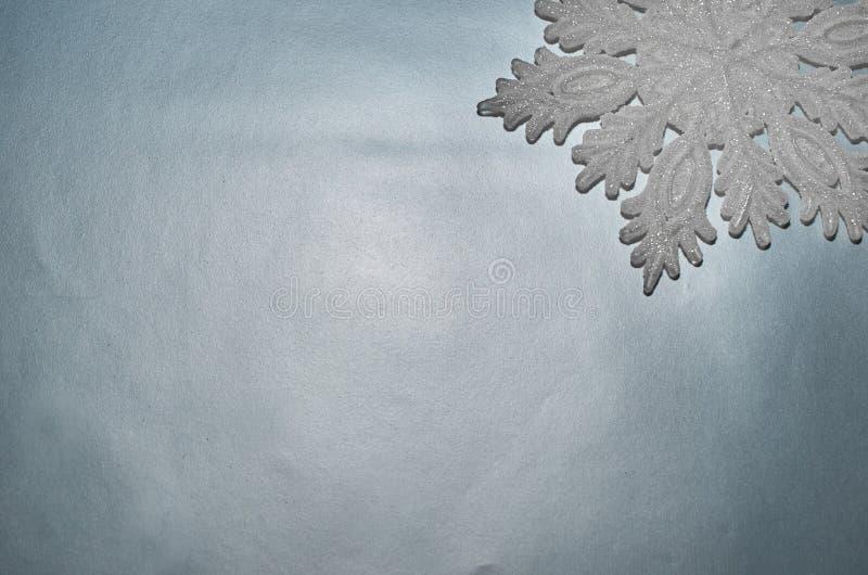 Διακοσμητικό snowflake βρίσκεται στο ασημένιο υπόβαθρο στοκ εικόνες